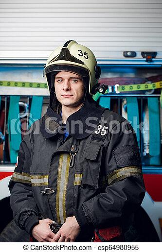 Foto de bombero con casco en el camión de bomberos - csp64980955