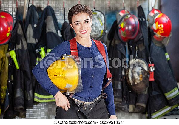 Feliz bombero sosteniendo el casco en la estación de bomberos - csp29518571