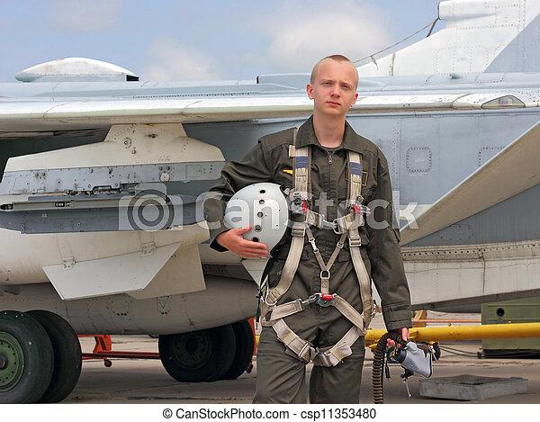 Piloto militar en un casco cerca del avión - csp11353480