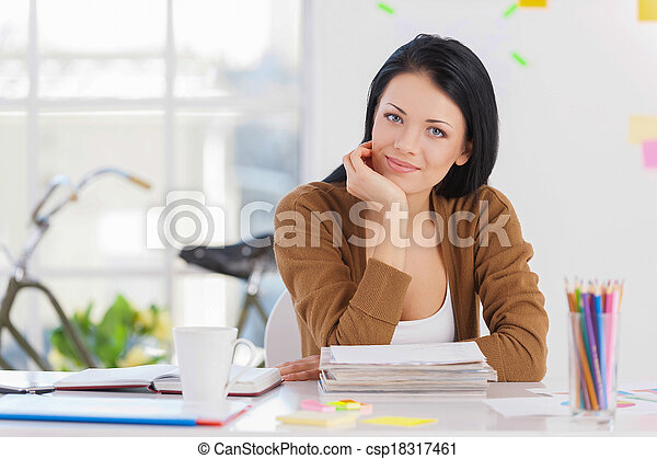 Casual business woman. Portrait of a beautiful young business woman sitting at her working place. - csp18317461