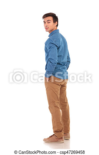 da111b7ab2 Full body picture of a casual man looking back over his shoulder on ...