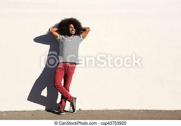 casual man standing outside with hands in hair relaxed - csp43753920