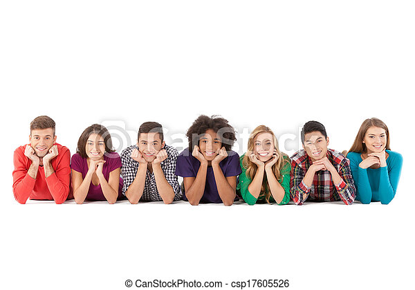 Casual people. Cheerful young multi-ethnic people lying on front and smiling while isolated on white - csp17605526