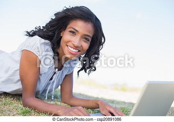 Casual pretty woman lying on the grass using her laptop - csp20891086
