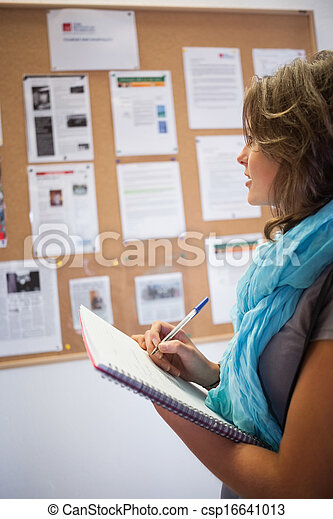 Casual student taking notes in front of notice board - csp16641013