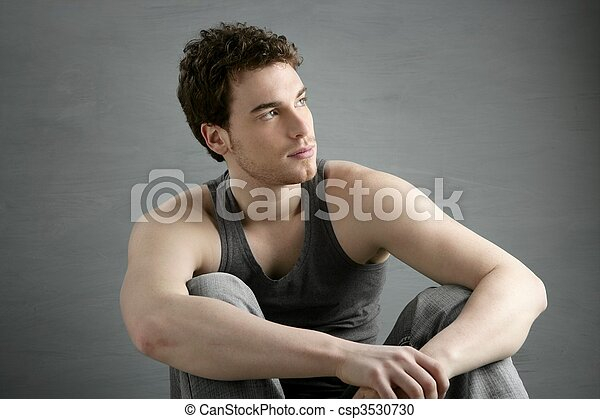 casual young man portrait sit over gray - csp3530730