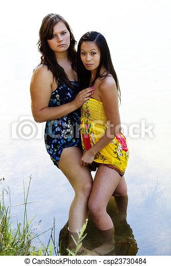 Caucasian And Asian American Women Standing In River - csp23730484