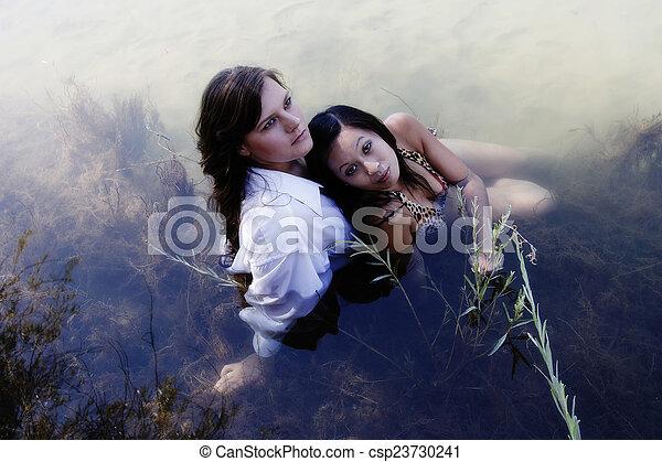 Caucasian And Asian American Women Sitting In River - csp23730241