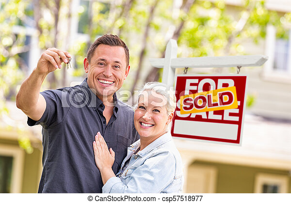 Caucasian Couple in Front of Sold Real Estate Sign and House with Keys - csp57518977