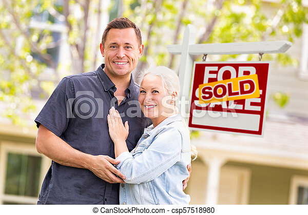 Caucasian Couple in Front of Sold Real Estate Sign and House - csp57518980