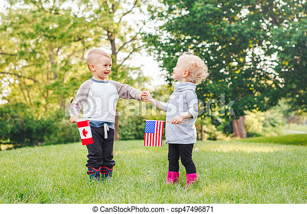 Caucasian girl and boy smiling laughing holding hands and waving American and Canadian flags - csp47496871