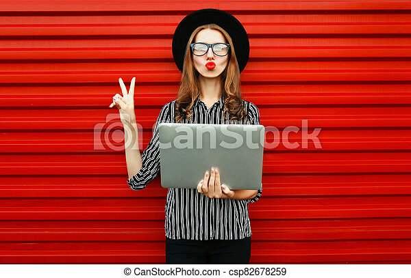Caucasian young woman with laptop on red wall background - csp82678259