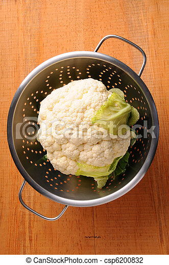 Cauliflower in Colander on rustic wood table - csp6200832