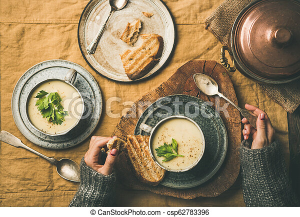 Celery cream soup in cups and female hands in sweater - csp62783396