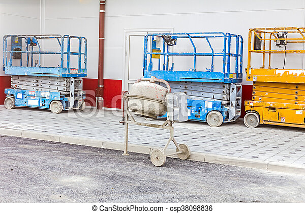 Cement mixer is placed next to a row of cherry pickers - csp38098836
