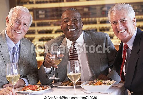 Amigos cenando juntos en un restaurante - csp7420361