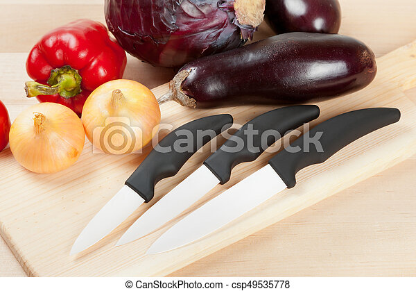ceramic knifes with vegetables on cutting board - csp49535778