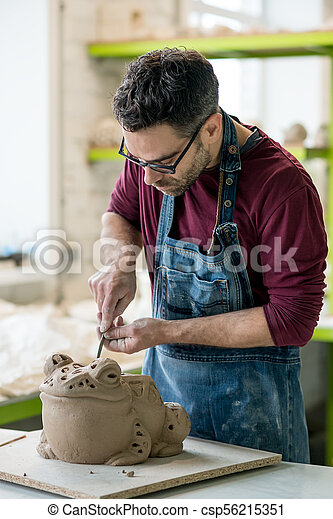 Ceramist Dressed in an Apron Sculpting Statue from Raw Clay in Bright Ceramic Workshop. - csp56215351