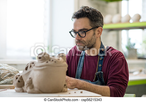Ceramist Dressed in an Apron Sculpting Statue from Raw Clay in Bright Ceramic Workshop. - csp56215343