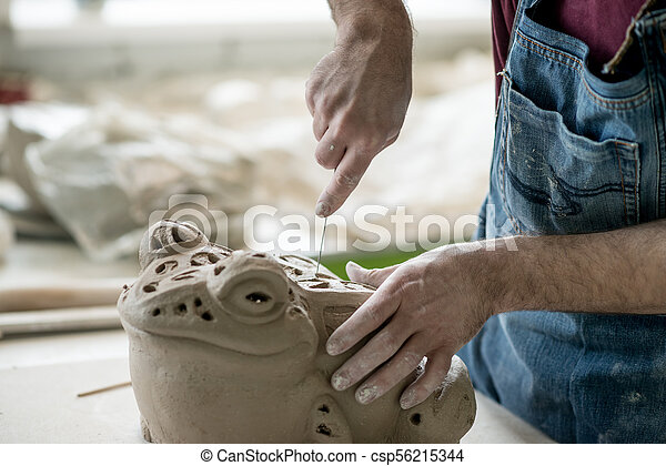 Ceramist Dressed in an Apron Sculpting Statue from Raw Clay in Bright Ceramic Workshop. - csp56215344