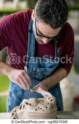 Ceramist Dressed in an Apron Sculpting Statue from Raw Clay in Bright Ceramic Workshop. - csp56215345