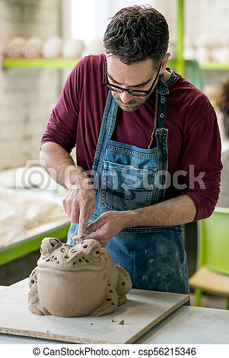 Ceramist Dressed in an Apron Sculpting Statue from Raw Clay in Bright Ceramic Workshop. - csp56215346
