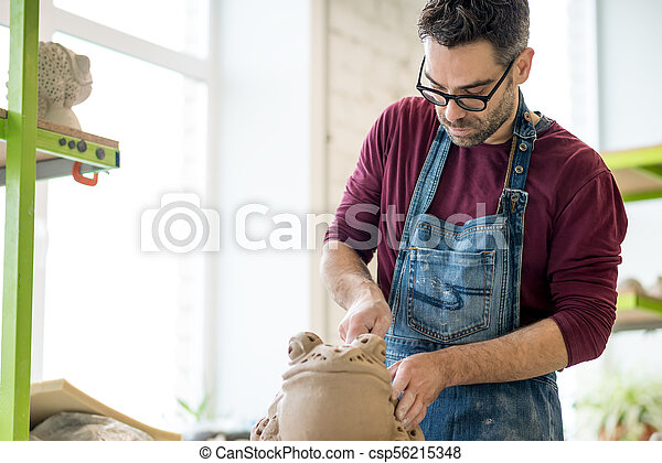 Ceramist Dressed in an Apron Sculpting Statue from Raw Clay in Bright Ceramic Workshop. - csp56215348