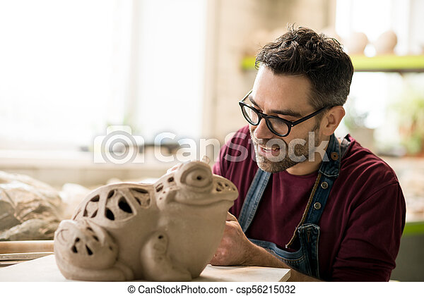 Ceramist Dressed in an Apron Sculpting Statue from Raw Clay in Bright Ceramic Workshop. - csp56215032