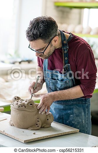 Ceramist Dressed in an Apron Sculpting Statue from Raw Clay in Bright Ceramic Workshop. - csp56215331