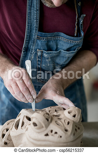 Ceramist Dressed in an Apron Sculpting Statue from Raw Clay in Bright Ceramic Workshop. - csp56215337