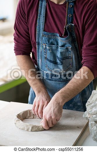 Ceramist Dressed in an Apron Working with Raw Clay in Bright Ceramic Workshop. - csp55011256