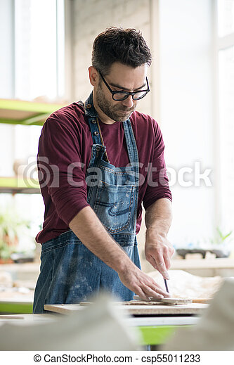 Ceramist Dressed in an Apron Working with Raw Clay in Bright Ceramic Workshop. - csp55011233