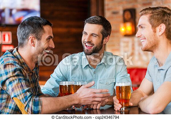 Reunión con los mejores amigos. Tres jóvenes felices con ropa informal hablando y bebiendo cerveza mientras están juntos en el bar - csp24346794