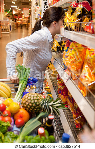 Una mujer con cesta de compras en el supermercado - csp3927514