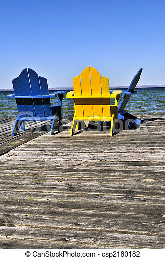 Chairs on wooden dock at lake - csp2180182