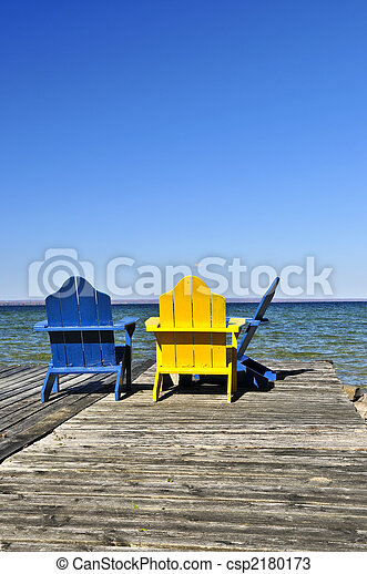 Chairs on wooden dock at lake - csp2180173