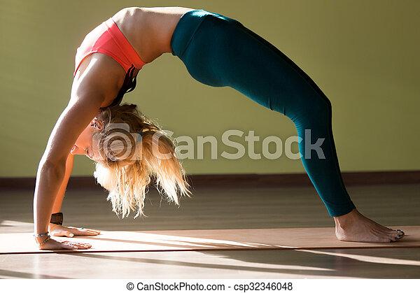 chakrasana yoga pose portrait of sporty beautiful blond