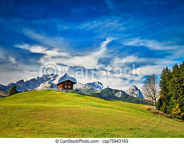 Chalet on a meadow at the mountain Eckbauer with alps - csp75943163