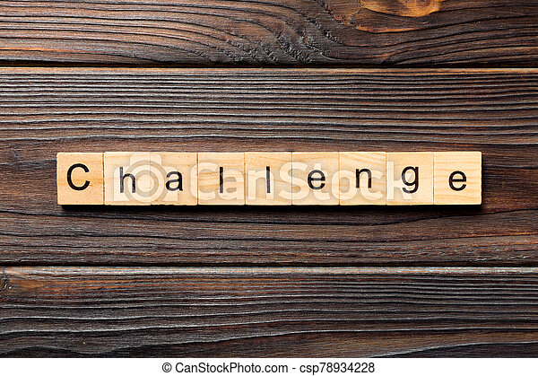 CHALLENGE word written on wood block. CHALLENGE text on wooden table for your desing, concept - csp78934228