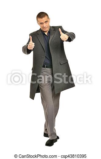 Hombre de abrigo mostrando pulgares arriba - csp43810395