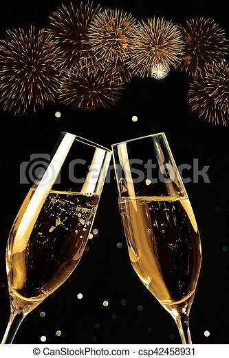 champagne flutes with golden bubbles make cheers with fireworks