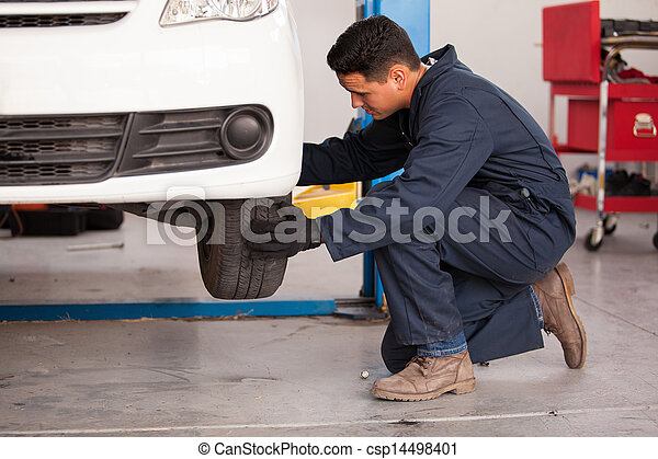 Changing a tire at an auto shop - csp14498401