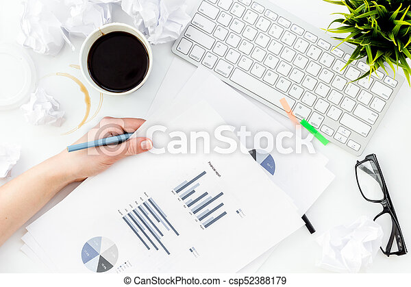 Chaos in office. Desk covered with crumpled paper and scattered stationery. Sheet with chart. White background top view - csp52388179