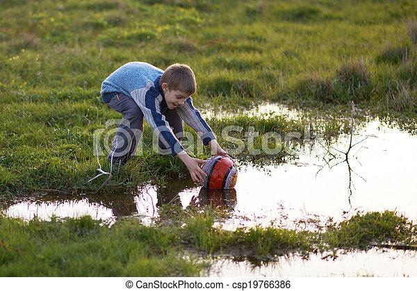 El chico recibe bola con charcos en la hierba - csp19766386