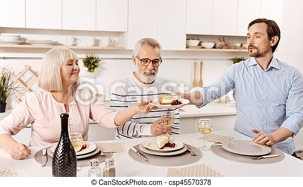 Charismatic man enjoying family dinner with parents at home - csp45570378