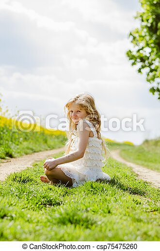 charming caucasian child sitting alone in spring nature - csp75475260