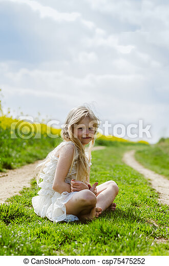 charming caucasian child sitting alone in spring nature - csp75475252