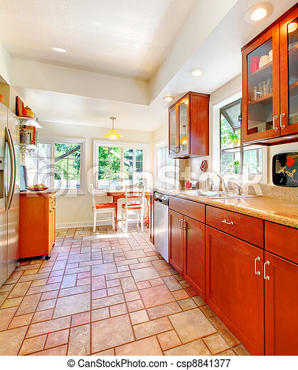 Charming cherry wood kitchen with tile floor. - csp8841377