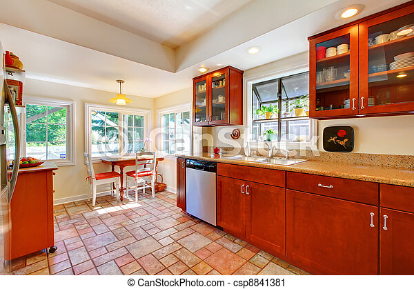 Charming cherry wood kitchen with tile floor. - csp8841381