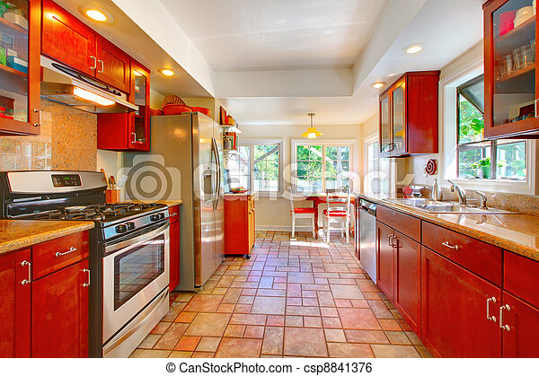 Charming cherry wood kitchen with tile floor. - csp8841376